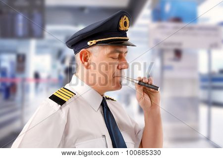 Airline pilot wearing uniform with epaulettes smoking electronic cigarette.