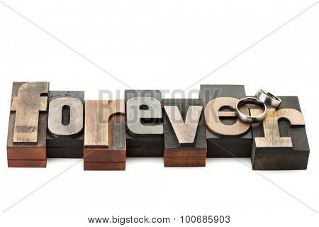 Wedding rings on the word Forever, written with vintage letterpress printing blocks isolated on white background