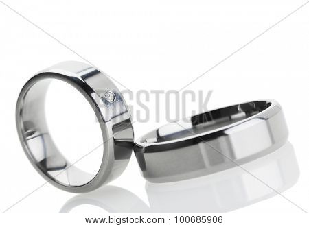 Wedding rings reflecting on white background, tilted view