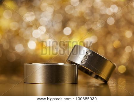 Pair of wedding rings, closeup, sparkling bokeh background