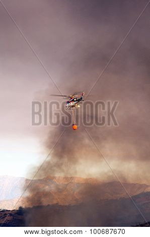 Helicopter fighting brush fire.