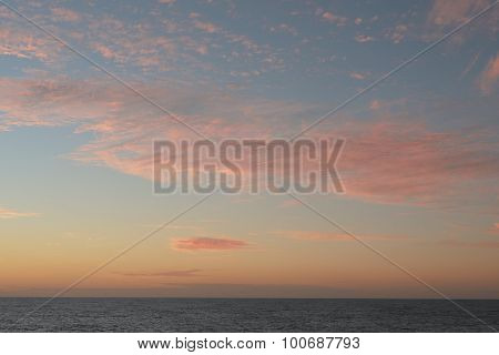 A soft cloud background with a pastel colored cloudscape. Summer evening sky background texture.