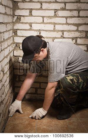 Builder Setting Tile On Cement Floor.