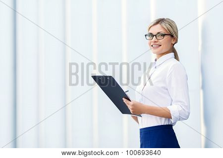 Cheerful business woman holding folder