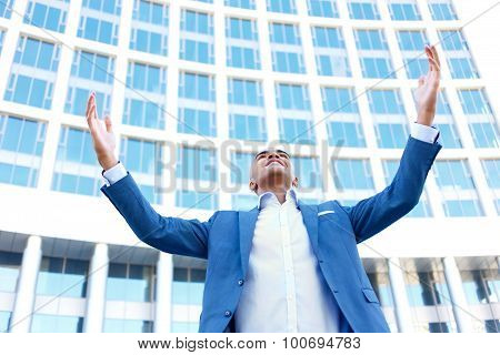 Pleasant businessman standing near office