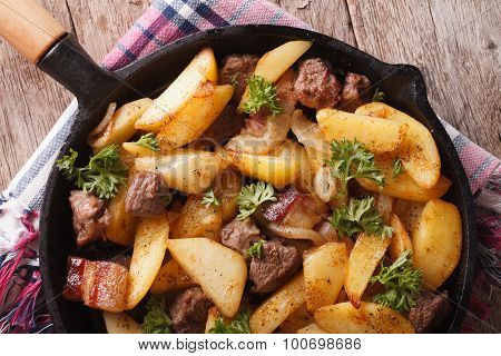 Fried Potatoes With Meat And Bacon In A Pan Close-up. Horizontal Top View