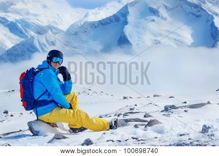 Snowboarder in helmet and goggles, with backpack sitting on the mountain rock