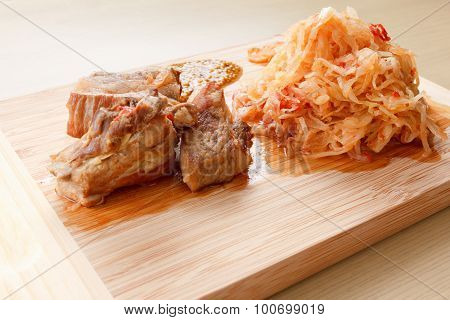 Few Roasted Pork Ribs With Tomato, Carrots And Cabbage On A  Cutting Board