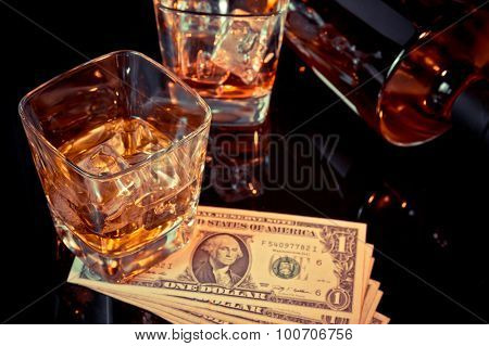 Glasses Of Whiskey Near Bottle And Dollars On A Black Table. Western Theme Style