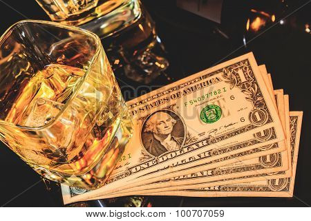 Top Of View Of Glasses Of Whiskey Near Bottle On Dollars Money On A Black Table. Western Theme Style