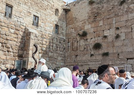 JERUSALEM, ISRAEL - OCTOBER 12, 2014: The area in front of Western Wall of  Temple filled with people. Elderly religious Jew with a Shofar. Morning autumn Sukkot
