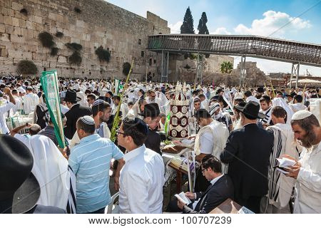 JERUSALEM, ISRAEL - OCTOBER 12, 2014: Morning autumn Sukkot. The area in front of Western Wall of  Temple. Crowd of Jewish worshipers in white wearing prayer shawls. On table there is Torah Roll.