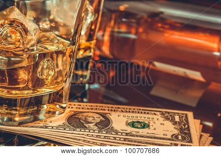 Close-up Of Glasses Of Whiskey Near Bottle And Dollars On A Black Table. Western Theme Style