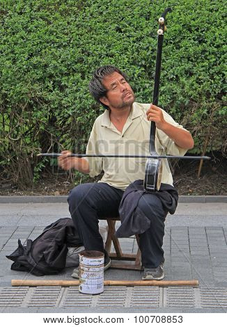 blind musician is playing on the street in Shanghai