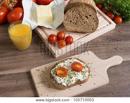 Wheat slice of bread with cheese and tomatoes on wooden board.