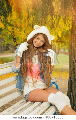 Smiling girl dressed in a cute knitted white bear hat resting in autumn park.