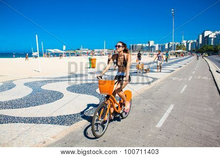 RIO DE JANEIRO, BRAZIL - APRIL 24, 2015: Young Brazilian woman rides her bicycle along the boardwalk at Copacabana Beach. Rio de Janeiro , Brazia.