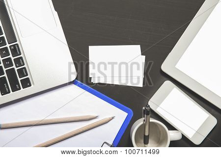 Laptop, Stationery, Mobilephone, And Business Card On Black Board Top View