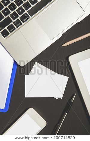 Business Card With Laptop, Stationery, Mobilephone, And Tablet On Blackboard Top View