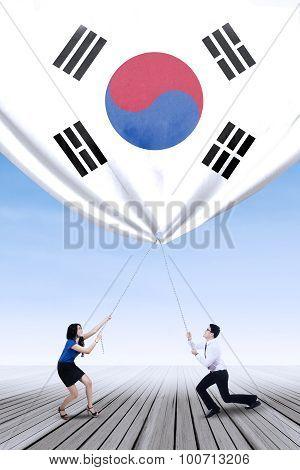 Korean Businesspeople Pulling Down A Korean Flag