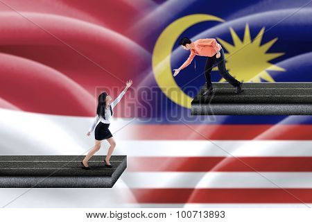 Man Helps Woman With Indonesian And Malaysian Flags