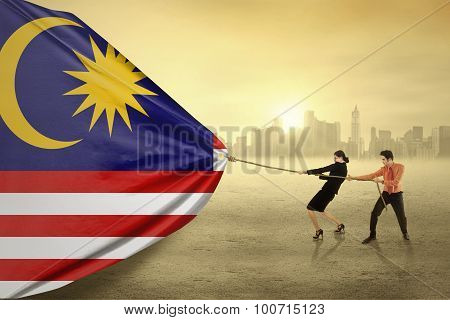 People Pulling A Flag Of Malaysia