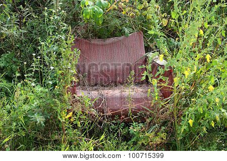 Thrown Red Armchair In The Grass