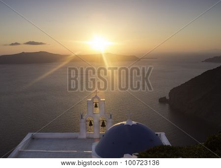 View of sunset over blue roofed church, Santorini