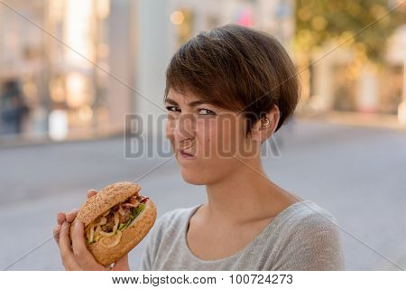Young Woman Grimacing In Distaste At A Burger