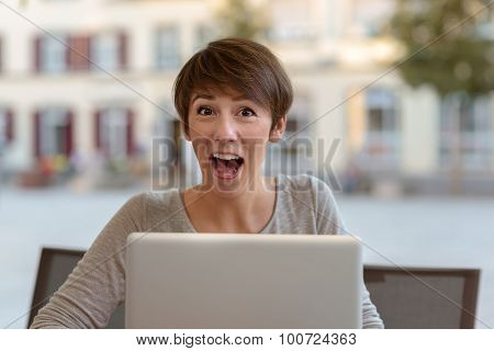 Excited Young Woman Reacting To News On Her Laptop