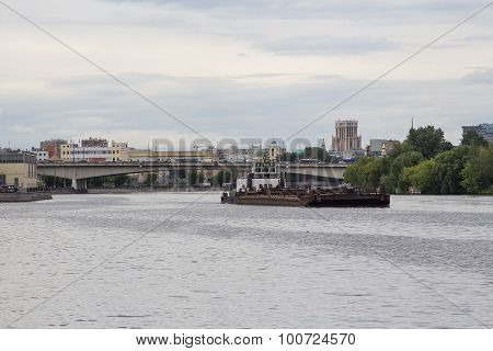 Tugboat Pushing A Heavy Barge On The River