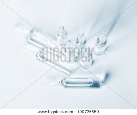 Top View Of Break-seal Glass Ampoule Set With Liquid Medicine On Light Blue Background.