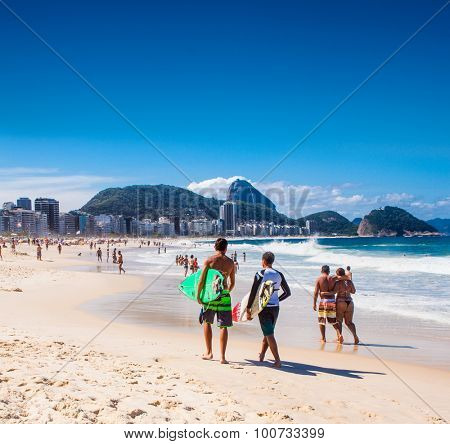 RIO DE JANEIRO, BRAZIL - APRIL 24, 2015: Surfers carry their surfboard on April 24, 2015 at Copacabana Beach, Rio de Janeiro. Brazil.