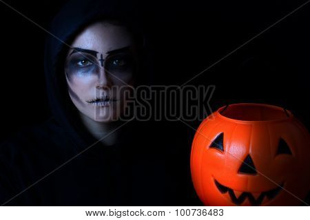 Girl Dressed In Scary Face Paint With Pumpkin Bucket On Black Background