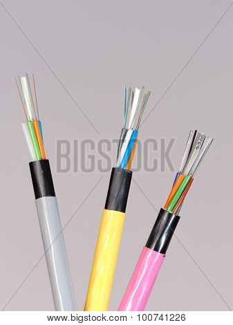 Different colored fiber optic cable ends with stripped jacket layers and exposed colored fibers