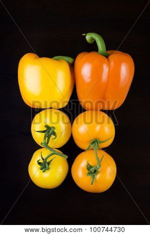 Yellow and orange bell peppers and tomatoes isolated on black background