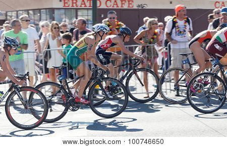 Side View Of A Grooup Of Triathetes Cycling