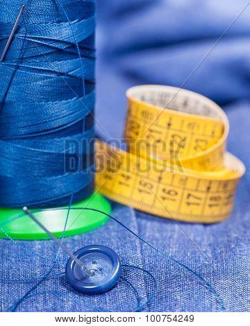 Thread Bobbin, Button, Measure Tape On Blue Dress