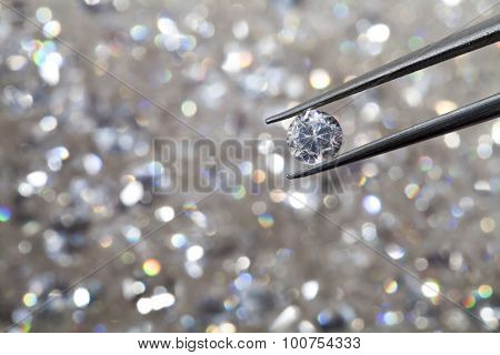 Diamond Held By Tweezers Close Up. More Diamonds Out Of Focus In Background.