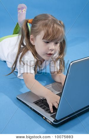 The Little Girl Is Using Computer On Blue