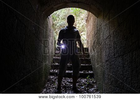 Young Man With A Flashlight Enters Stone Tunnel