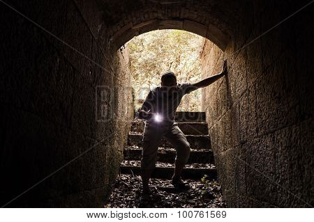 Young Man With A Flashlight Enters The Stone Tunnel