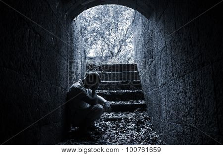 Young Sad Man Sitting Inside Of Dark Stone Tunnel