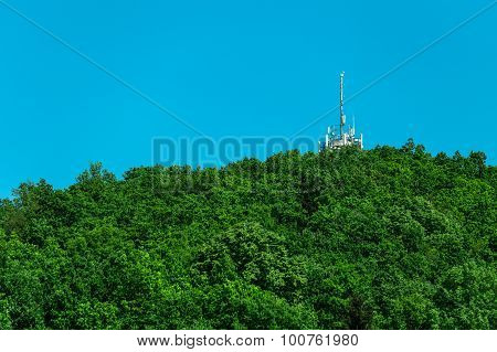 Telecommunication transmitter in the mountain among trees