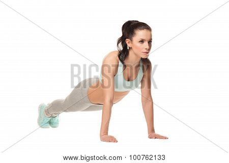 Athletic Woman Doing Push-ups On A White Background. Fitness Model With A Beautiful, Athletic Body
