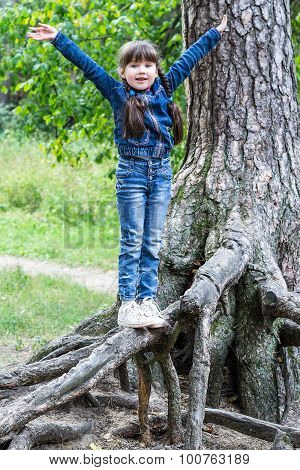 Little Cheerful Girl Teetering On The Roots Of A Tree