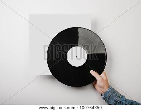 Male hand holding vinyl music album template on white wall backg