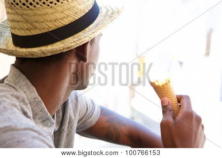 Young Man With Hat Eating Ice Cream