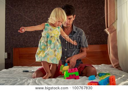 Little Girl Hands Sideward Stands By Father On Sofa