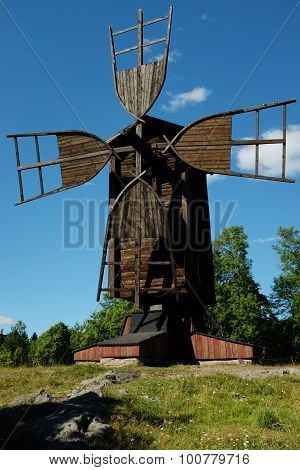 Ancient Wooden Windmill Against The Blue Sky